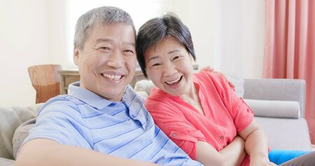 asian eldely couple smile to you happily at home 版權商用圖片 - 129773802