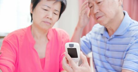 asian elder couple use blood glucose meter and worry about it - Prevention diabetes concept