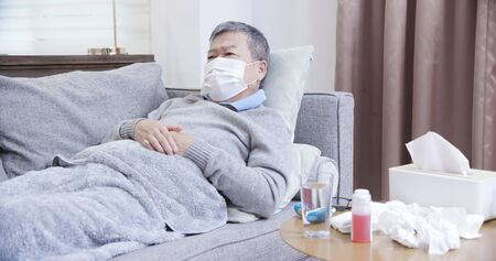 asian eldely sick man wear mask lying on the sofa at home