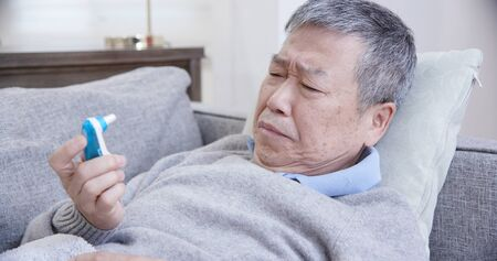 asian eldely man get sick and use thermometer lying on the sofa at home 스톡 콘텐츠