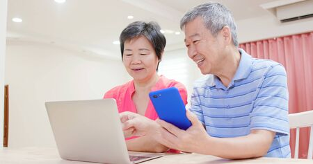 asian elder couple use smart phone and talk about it