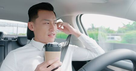 relaxed business asian man experience to riding an autonomous self driving car and drink a coffee in highway Foto de archivo - 129773811
