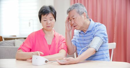 asian elder couple use manometer to test blood pressure and they worry about it