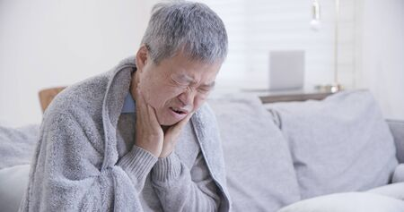 asian elderly man has sore throat and feel very uncomfortable at home