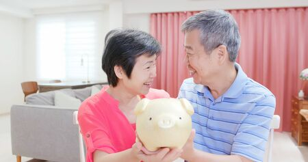 Good Retire plan concept - eldely couple hold piggy bank smile happily at home