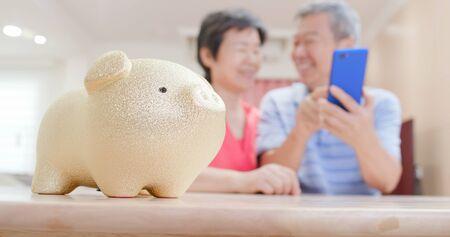 Perfektes Konzept für den Ruhestand - Nahaufnahme von Sparschwein und altes Ehepaar verwenden Smartphone glücklich zu Hause Standard-Bild