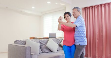 asian eldely couple dance together happily at home
