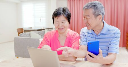 asian elder couple use smart phone and laptop at home