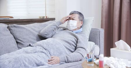 asian eldely man get sick and wear mask lying on the sofa at home
