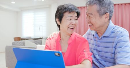 asian elderly couple use digital tablet happily at home