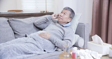 asian eldely man get sick and lie on the sofa using thermometer at home
