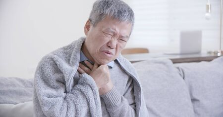asian elderly sick man has sore throat and feel very uncomfortable at home 免版税图像 - 130165360