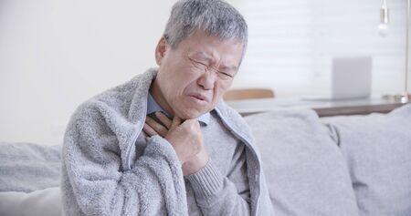 asiatischer älterer kranker Mann hat Halsschmerzen und fühlt sich zu Hause sehr unwohl