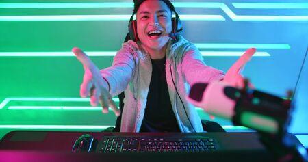 Jeune vlogger asiatique beau ayant une diffusion en direct et jouant dans un jeu vidéo en ligne Banque d'images