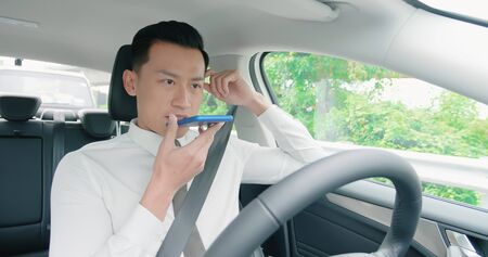 asian young man speak to voice assistant with smart self driving car on the freeway