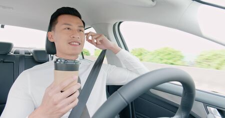 relaxed business asian man experience to riding an autonomous self driving car and drink a coffee in highway Фото со стока