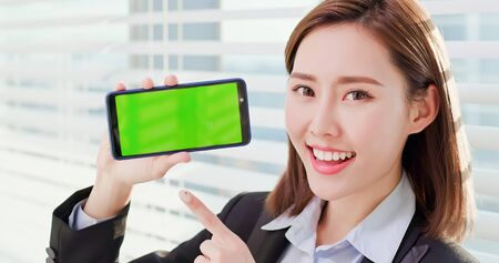 Young asian business woman show green screen with smart phone