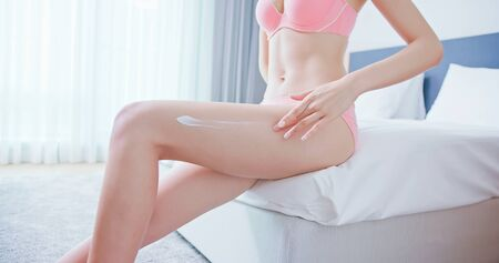 Skin care concept - beauty woman apply cream onto her leg and sit on bed at home