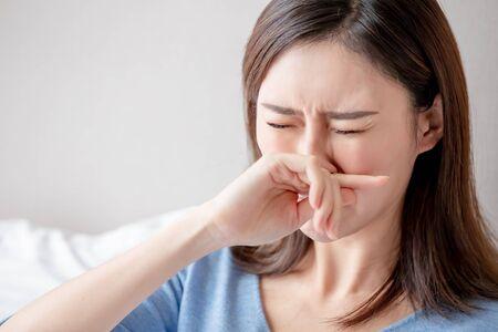Asiatin krank und niesen im Schlafzimmer