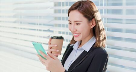 business woman use smart phone and drink coffee happily in office