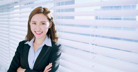 zelfverzekerde Aziatische zakenvrouw lacht naar je op kantoor
