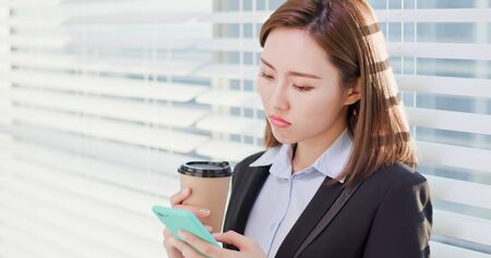 business woman feel depress and use smart phone while drinking coffee in the office Stok Fotoğraf