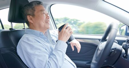 asian elderly man experience self-driving smart car and has a cup of coffee