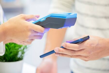 mobile payment concept - close up of pay bills by Phone to Credit Card System 版權商用圖片 - 130672900