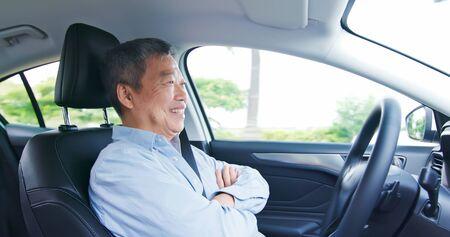 asian elderly man experience to drive an self-driving smart car Фото со стока