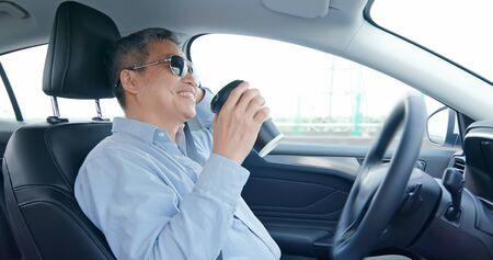 asian elderly man experience self-driving smart car and has a cup of coffee Фото со стока