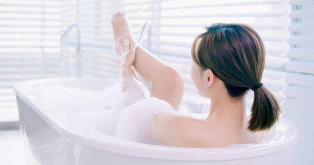 donna asiatica che fa un bagno di bolle e si tocca la gamba Archivio Fotografico
