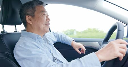 asian elderly man driving happily in the car on highway