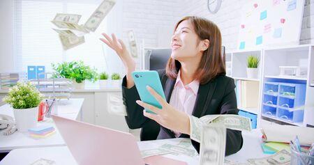 Aziatische zakenvrouw opgewonden met regenend geld