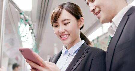 Asian Business people use smart phone on the mrt Stock Photo