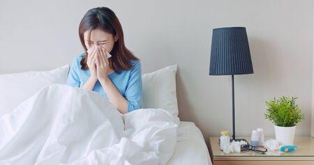 Aziatische vrouw ziek en nies met papieren zakdoekje in de slaapkamer Stockfoto