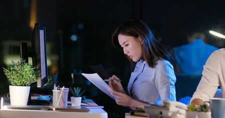 asian businessman and businesswoman overtime work and read the documents in the office Banco de Imagens