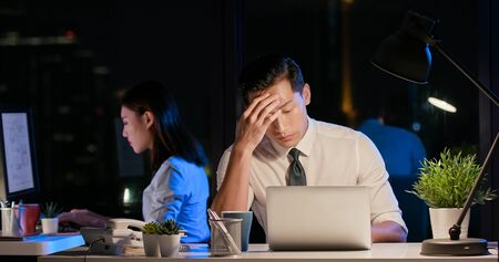 asian businessman overtime work and has headache in the office