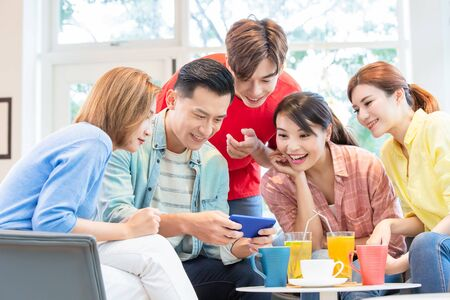 asian man play games on smart phone and friends are happily