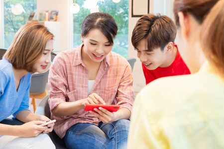 asian woman and man watch video on smart phone happily