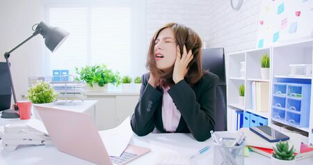 Business asian woman stressed and overworked yelling in office