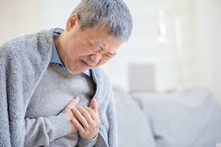 asian elderly sick man feeling sharp strong pain because of heart attack Stock Photo - 131538096