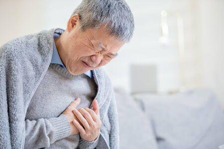 asiatischer älterer kranker Mann, der wegen eines Herzinfarkts starke starke Schmerzen verspürt Standard-Bild