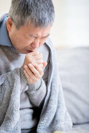 Aziatische bejaarde zieke man is verkouden en hoest thuis Stockfoto