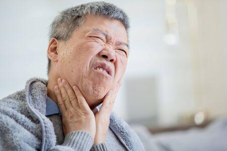 Nahaufnahme eines asiatischen älteren kranken Mannes hat Halsschmerzen und fühlt sich zu Hause sehr unwohl