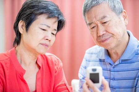 close up of asian elder couple use blood glucose meter and worry about it - Prevention diabetes concept Banco de Imagens - 131538117