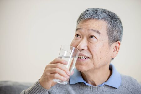 close up of asian old man drink water and feel good at home
