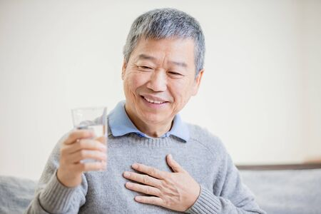 asian old man drink water and feel good at home