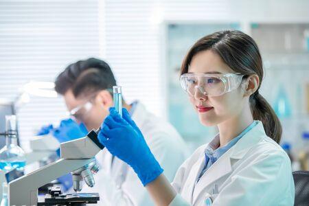 une femme scientifique asiatique tient un tube à essai rempli de liquide dans le laboratoire