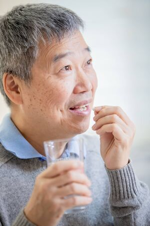 close up of asian old man take medicine  at home