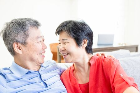 asian eldely couple smile to each other happily at home